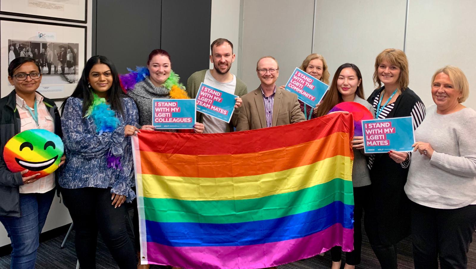 IPC Health staff holding rainbow flag and IDAHOBIT Day signs