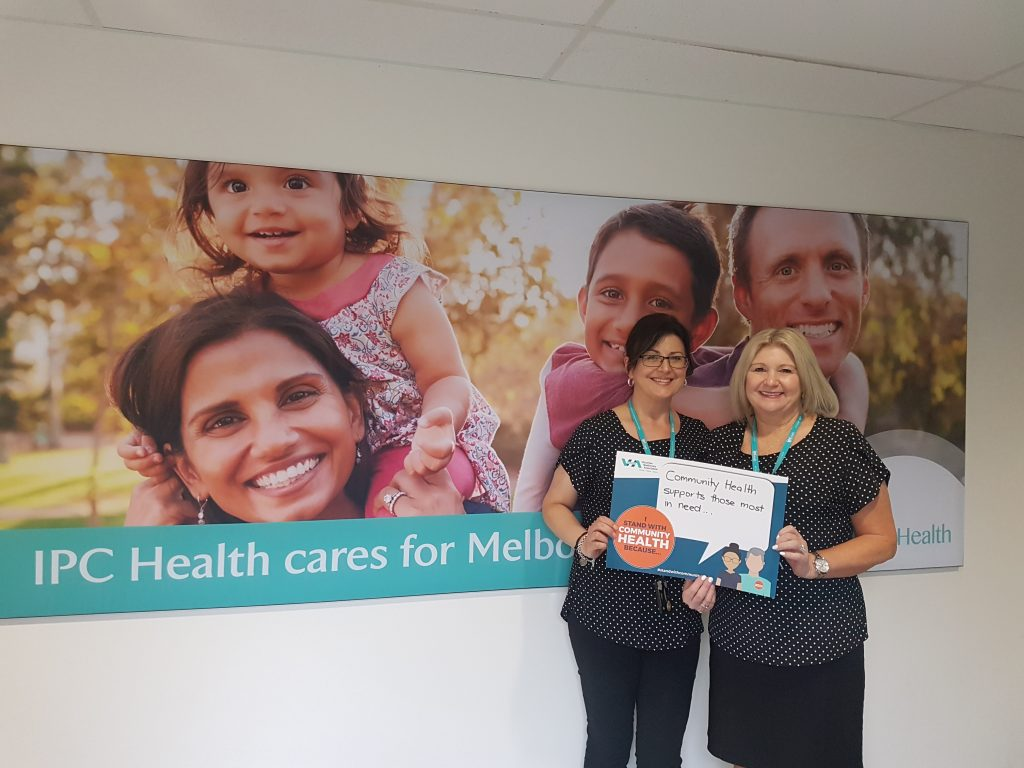 Two IPC Health staff holding Community Health campaign sign on front of IPC Health brand board