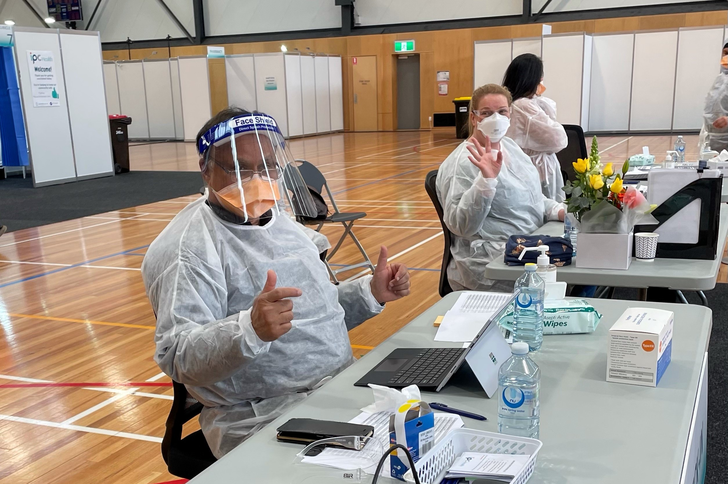 people in protective gear sitting at tables