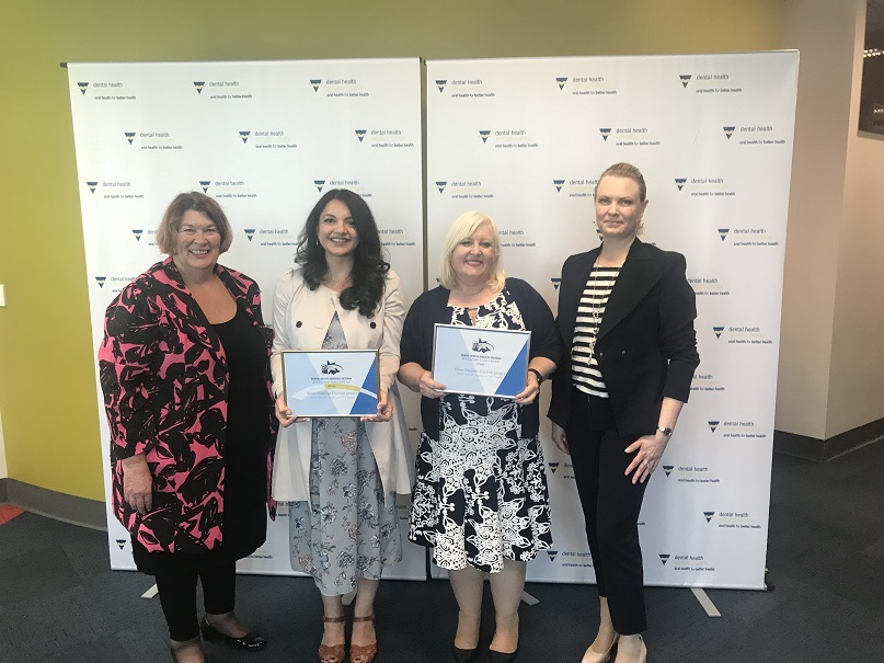 Women holding up Dental Health Victoria awards 2018